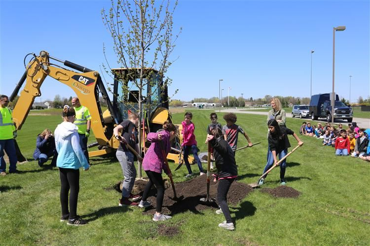 4th grade students help shovel more dirt in to plant tree