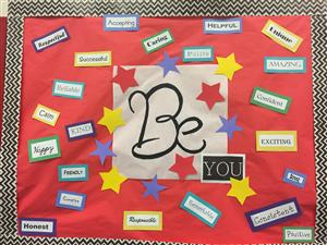 Bulletin Board in the LRC telling kids to be happy, accepting, caring, and other various character traits.