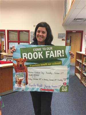 Mrs. Seiple, showing our Book Fair Poster.