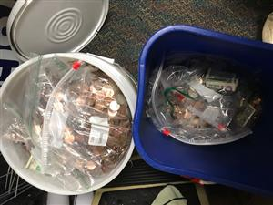 A five gallon bucket filled to the top with coins and a smaller blue recycle bin also filled with coins